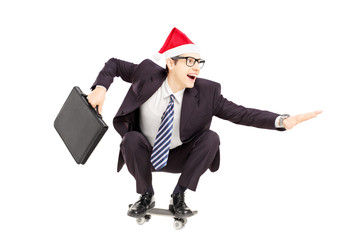 Businessman with briefcase and santa hat riding a skateboard