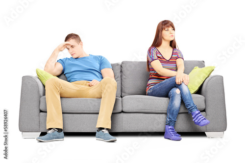 Sad heterosexual couple sitting on a sofa after an argument