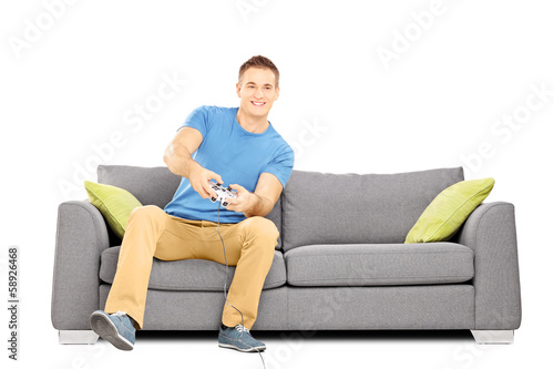 Young smiling man seated on a sofa playing video games