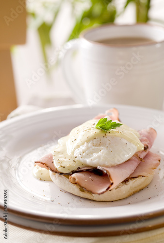 Breakfast table with Eggs Benedict and coffee.