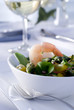 Closeup of a fresh salad topped with shrimp.