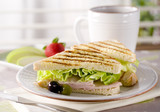 grilled panini, fruit and a cup of coffee.