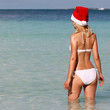 Santa Girl on Tropical Beach. Beautiful blonde young woman