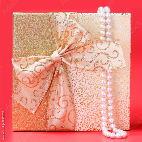 Gift Box with Pearl Necklace over red background. Christmas