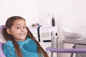 pretty little girl in dentist chair waiting for doctor