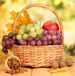 Grape in basket with nuts on wooden table