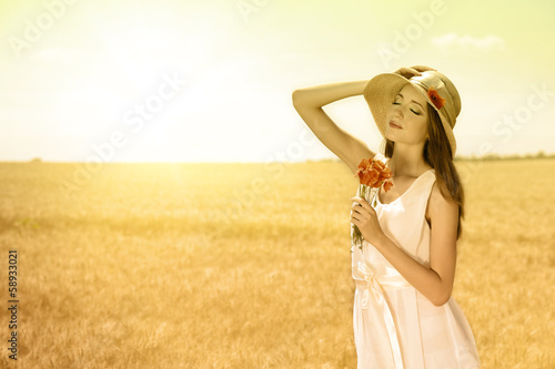 Portrait of beautiful young woman with poppies in the field