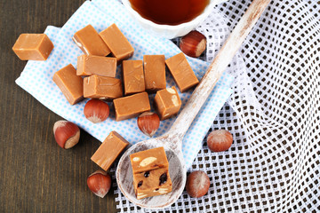 Many toffee in spoon and cup of tea on napkins on wooden table