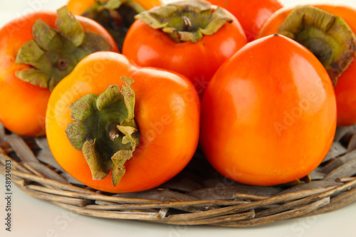 Ripe persimmons on wicker stand close up