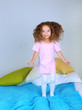 Little girl jumping on bed
