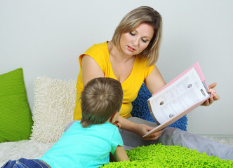 Little boy with mom read book in bed