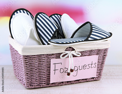 Slippers in basket on table on bright background