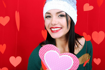 Attractive young woman with card on Valentine Day