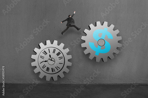 Businessman jumping on 2 large concret gear