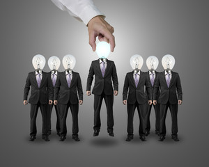 Hand lift one businessman with lighting bulb head in group
