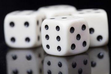 Four white dices in a black background