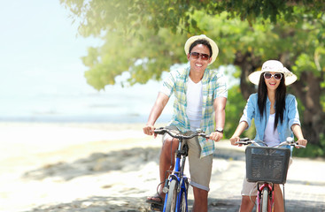 couple having fun riding bicycle at the beach