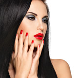 Face of a beautiful woman with red nails and lips