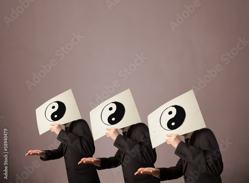 Handsome people in formal gesturing with yin yang sign on cardbo