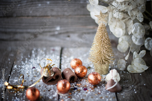 Christmas card with Christmas tree, chocolates on wooden board.
