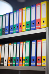 colorful folders on bookshelf