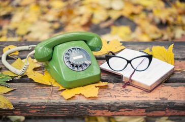 green vintage phone, book and glasses on bench in autumn park