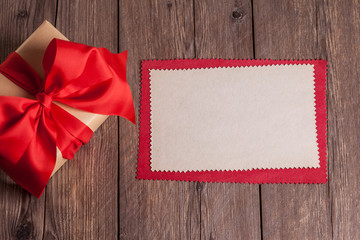 sheet of paper with gift box on wooden background