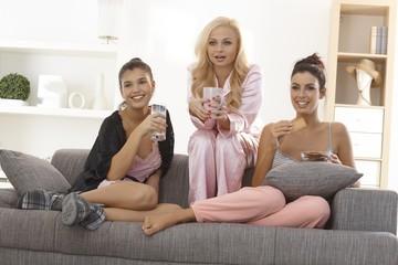Female friends watching tv in pyjamas