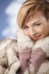 Beautiful young woman wearing fur coat