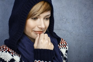 Thoughtful young woman in hooded sweater