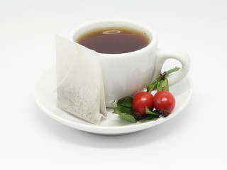 Teacup with teabag and rose hips