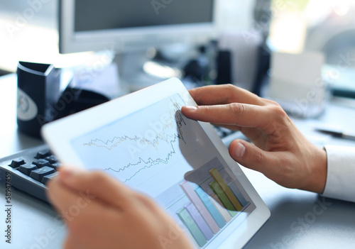 person analyzing statistics displayed on the tablet