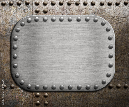 Rough metallic plate over rusty metal background.