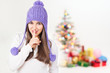Christmas girl with purple beanie gesturing hush