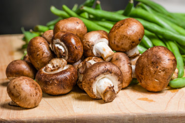 Mushrooms and green beans on a wooden board