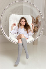 Girl sitting in a chair suspended round