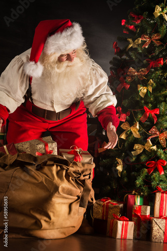 Santa Claus opening his sack and taking gifts under Christmas tr