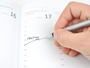 Hand with a pen and schedule