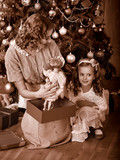 Kid with mother receiving gifts under Christmas tree.