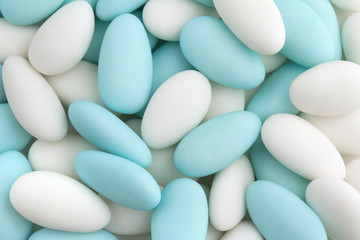 background of white and blue sugared almonds