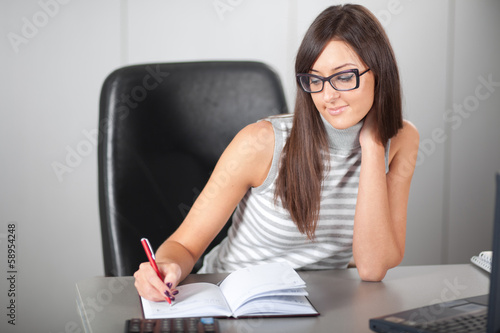 Pretty girl writing in the office