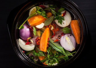 Fresh soup in a pot on black background