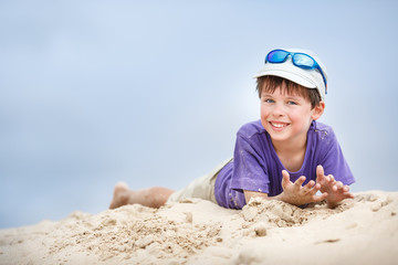 Cute little boy having fun on sandy beach