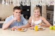 Couple has breakfast in the modern comfortable kitchen