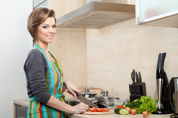 Woman in striped apron cooks in the modern comfortable kitchen