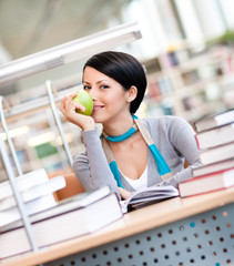 Female student with green apple studies