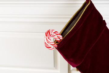 Christmas Stocking with Real Candy Canes hanging on Fireplace Ma