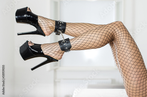 Sexy legs with fishnet stockings, ankle cuffs and platform shoes