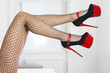 Legs of a woman wearing fishnet stockings and extreme red platfo