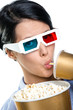 Girl in 3D spectacles drinking beverage and eating popcorn